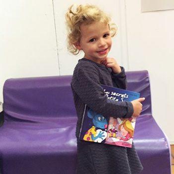 Petite fille tenant un livre sous son bras