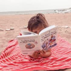 Enfant en train de lire sur la plage